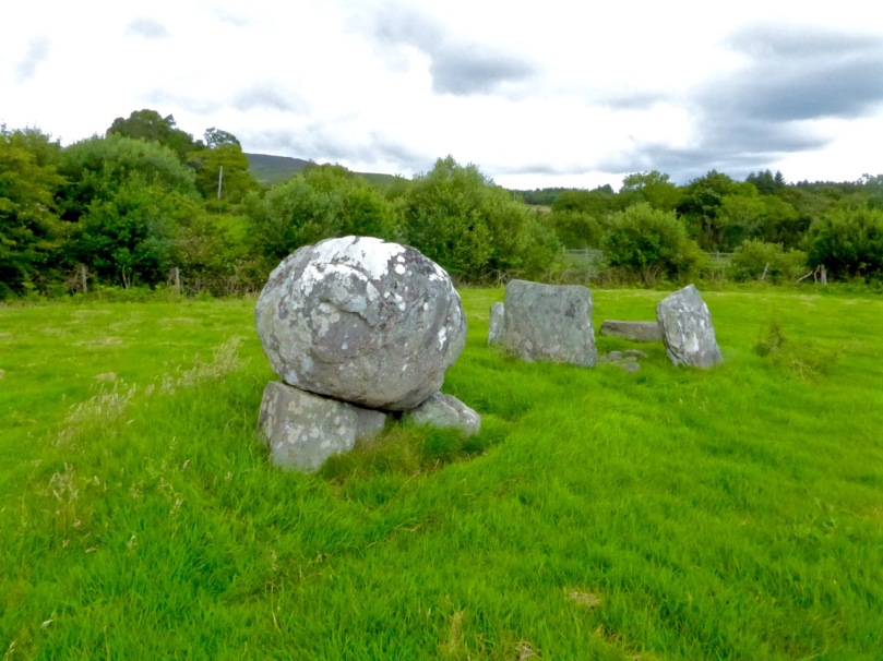 Boulder burial showing support stones. Five-stone circle in the background